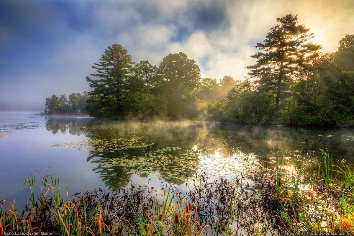 The sun breaks through the mist at Echo Lake in Dexter, Maine