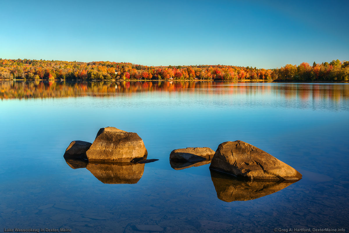 The large boulders create an interesting composition with the multi-colored autumn leaves and reflections on the surface of the very calm water.