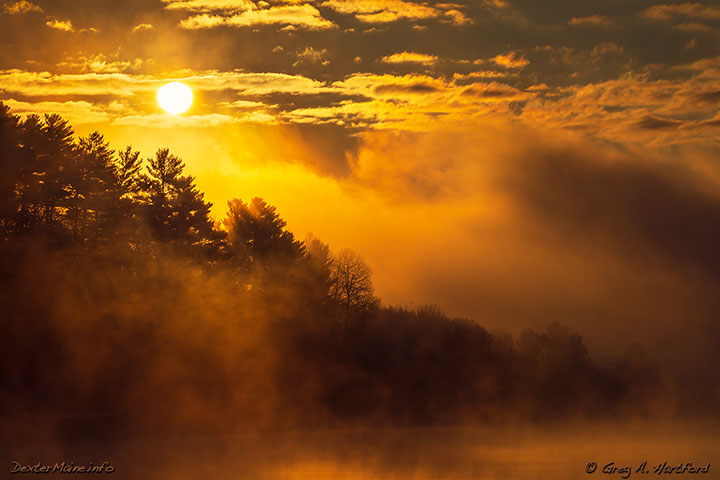Early morning sun breaks through the fog on Lake Wassookeag in Dexter, Maine