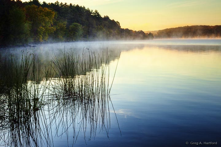 Sunrise on Lake Wassookeag with morning mist over the water